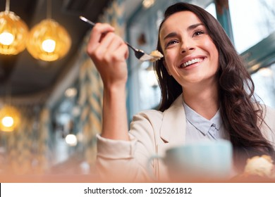 Ideal lunch. Low angle of gay attractive cute woman enjoying lunch while drinking coffee and smiling
