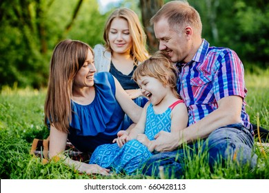 Ideal picture of family happiness - happy family with two daughter having fun and lying on the grass on a summer day in sunset. Parenthood, love, vacation and happy family concept.