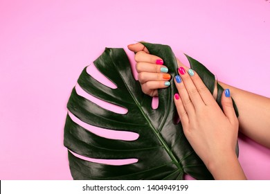 Ideal trendy neon manicure with green monstera leaf on pink background. Beauty concept.