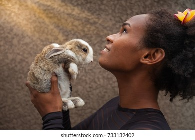 Idealistic young afro american woman daydreaming with Christmas bunny rabbit in her hands, feeling blessed