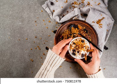 Ideas for an autumn winter breakfast. Spicy yoghurt with granola, dried berries, nuts, almonds, spices (cinnamon, anise), in cup, plate. Gray background, girl hold mug in hands. Top view copy space