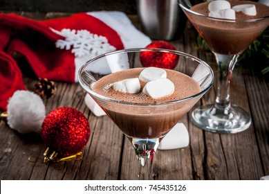 Ideas for Christmas party drinks, homemade Hot Chocolate Martini cocktails with marshmallow, on old rustic wooden table with christmas decorations, copy space