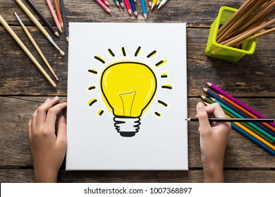 Ideas Concept , Hand of girl drawing a light bulb on paper and colorful pencils on old wooden table