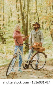 Ideas for perfect autumn date. Couple in love ride bicycle together in forest park. Romantic date with bicycle. Bearded man and woman relaxing in autumn forest. Romantic couple on date. Date and love.