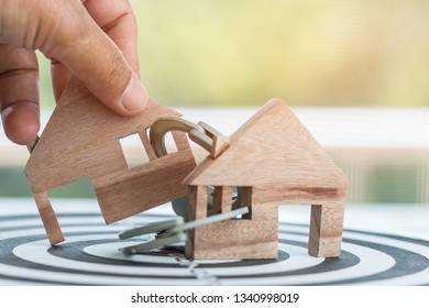 Ideas for real estate business fraud, financial risk or debt default, lacking financial freedom until being indebted and imprisoned. Handcuffs lock wooden shape house on dart board number target.