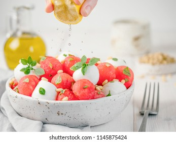 Ideas and recipes for healthy summer lunch food - watermelon caprese salad with mozzarella and basil. Watermelon balls and mini mozzarella balls on white wooden tabletop. Copy space for text.