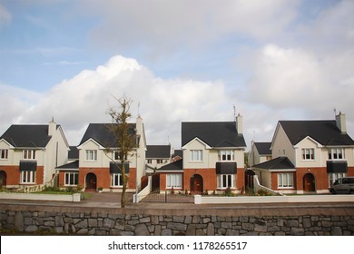 identical tricolor cottages in a cozy suburb, municipal district densely built over, economy class housing, Ireland, wide angle shot