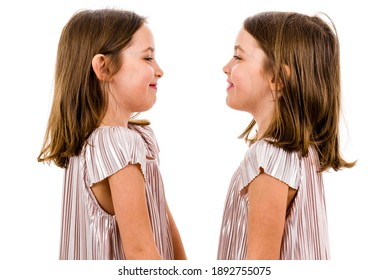 Identical twin girls are looking at each other and smiling. Concept of family and sisterly love. Profile side view of twin sisters in dresses looking at each other. Studio shot isolated on white.