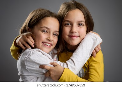 Identical twin girls sisters are posing for the camera. Happy twin sisters looking at the camera, laughing, smiling, hugging, holding hands. Professional frontal studio shot on gray / grey background