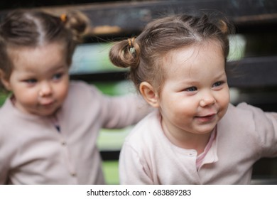 Identical twin girls smiling outdoors