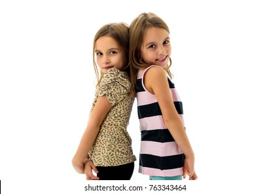 Identical twin girls are turned facing back to back. Concept of family and sisterly love. Profile side view of sisters playing, smiling and laughing.