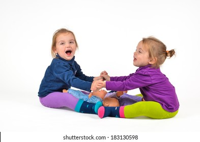 Identical twins babies exercising with Dolls and laughing. Children are exercising and are doing physical activity.