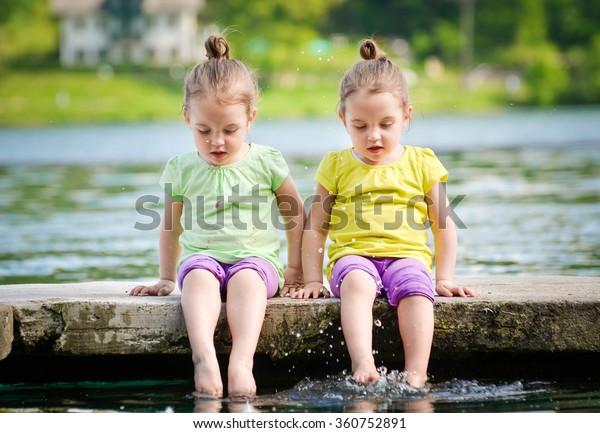 Las mellizas idénticas hacen ejercicio en la orilla del lago, espolvoreando agua. Niños sentados al lado del lago, jugando con agua. Estilo de vida saludable y activo para los niños.