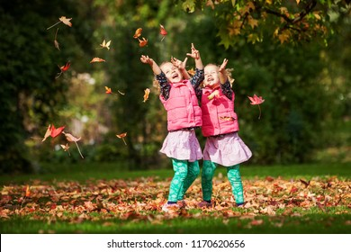 Identical twins having fun with autumn leaves, blond cute curly girls, happy family, beautiful girls in pink jackets, young family in park in autumn, healthy livestyle, autumn colourful leaves