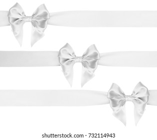 Identical white satin bow with tails on ribbon for Christmas gifts on white background