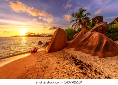 An identified romantic couple on shoreline near shaped granite stones of Anse Source d'Argent with sunset sky. Seychelles honeymoon. Sunlight over the sea on the horizon in La Digue, Seychelles.