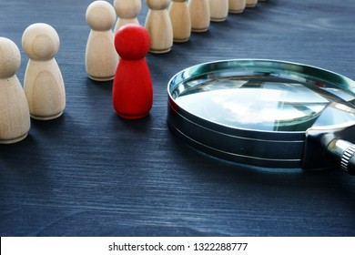 Identify concept. Recruitment and talent management. Red figurine and magnifier.