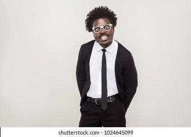 Idiotic afro man in white glasses grimacing at camera. Studio shot, gray background