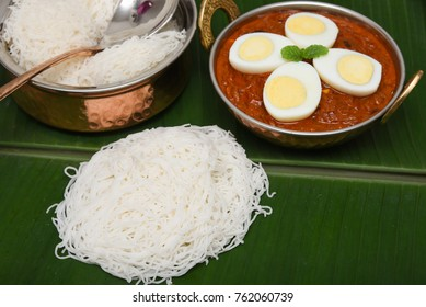 Idiyappam or string hoppers or Noolputtu with Kerala Eggs roast curry dish on banana leaf Kochi, India. A delicious south Indian non-vegetarian hot and spicy Masala recipe with meat, tomato and spices