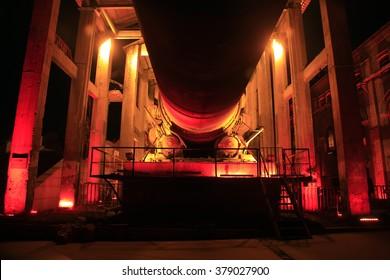 idle cement plant rotary kiln machinery at night, closeup of photo