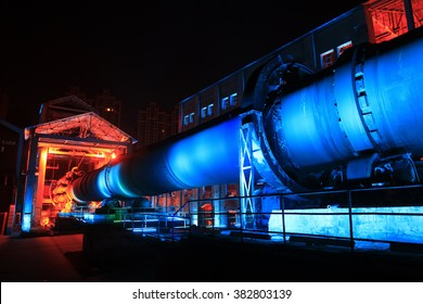 idle cement plant rotary kiln machinery at night, closeup of photo