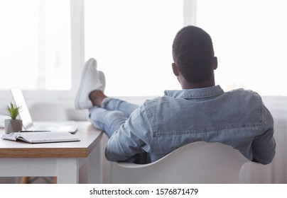 Idle time concept. Rear view of lazy african american employee sitting with his legs on work desk and looking to window, copy space