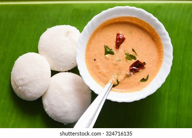 Idli  /idly traditional breakfast in South India. made by steaming batter of fermented black lentils de-husked and rice.served with vegetarian side dish Sambar, coconut chutney, pure ghee in Kerala