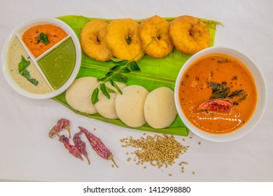 Idli and Medu wada with chutney and sambar on banana leaf