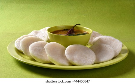 Idli with Sambar in bowl on green background, Indian Dish : south Indian favourite food rava idli or semolina idly or rava idly, served with sambar and green coconut chutney.