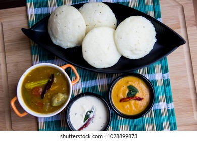idli, sambar, Tomato chutney, and coconut chutney with wooden background , south indian breakfast