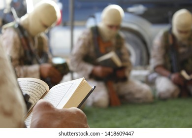 idlib , north / syria - 7 june 2019 : a group of syrian rebels reciting the holy book of quran during ongoing battles against syrian regime forces backed by russian army.