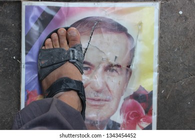 idlib, north / syria - march 11 2019 :  oppostion rebel stepping over picture late syrian dictator (hafiz al assad) picture.