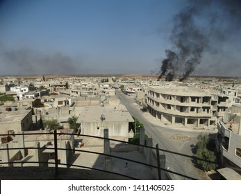 idlib , north / syria - may 29 2019 : black smoke of conflict in syria which affected civil areas as well and caused refugees to be displaced by force.