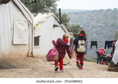 Idlib, Syria - 3 September 2014; Two Syrian refugee girls walking at the refugee camp. There are lots of tents around them