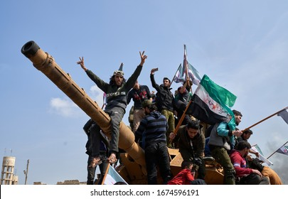 IDLIB, SYRIA, Syrians in protest climb atop a Turkish military M60T tank as they attempt to block traffic on the M4 highway on March 15, 2020.