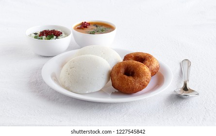 Idly or idli, is a healthy Indian, vegetarian, traditional and popular steam-cooked rice cakes, and vada, for breakfast, with chutney and sambar as side dishes.