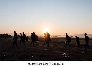 Idomeni, Greece - August 29, 2015. Silhouettes of refugees are seen walking inside a field as they cross the Greek Macedonian border.