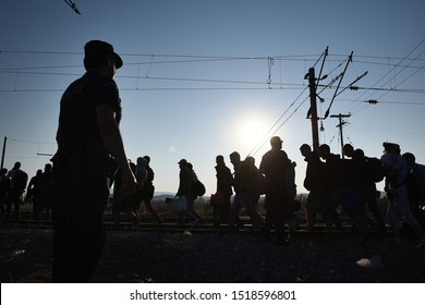Idomeni, Greece - August 29, 2015. A police officer stands guard as silhouettes of refugees cross the Greek Macedonian border.