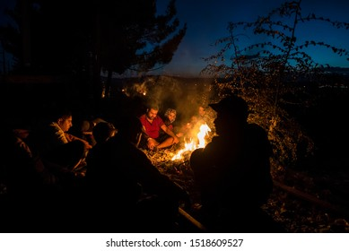 Idomeni, Greece - August 29, 2015. A group of Syrian refugees are warming up around a bonfire as they wait to pass the Greek Macedonian border.