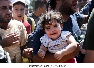 Idomeni, Greece - August 29, 2015. A Syrian refugee girl cries in his father's arms as refugees wait to cross the Greek Macedonian border.