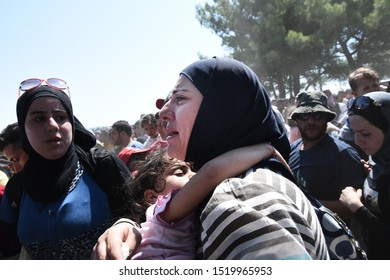 Idomeni, Greece - August 29, 2015. A Syrian refugee woman carries her daughter as refugees cross the Greek Macedonian border.