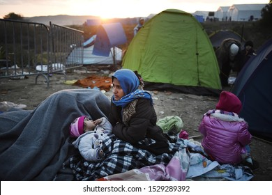 Idomeni, Greece - December 4, 2015. A refugee woman with her children try to keep warm at the makeshift refugee camp of Idomeni at the Greek-Macedonian border.