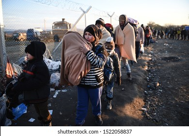 Idomeni, Greece - December 5, 2015. Refugees stand next to a border fence as they wait to cross the Greek Macedonian border.