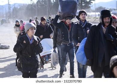 Idomeni, Greece - February 17, 2016. Refugees carry their belongings as they cross the Greek Macedonian border.