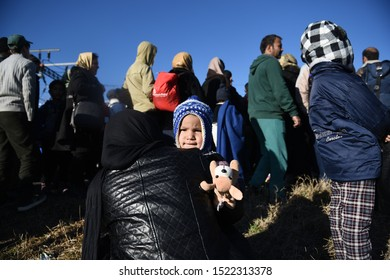 Idomeni, Greece - February 17, 2016. A refugee boy stands on his mother's arms as refugees wait to cross the Greek Macedonian border.