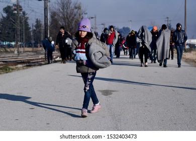 Idomeni, Greece - February 17, 2016. A refugee girl carries a blanket as refugees arrive at the makeshift refugee camp of Idomeni in order to cross the Greek Macedonian border.