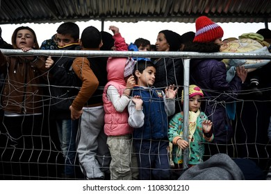 Idomeni, Greece - February 29, 2016. Refugee kids wait in line with other refugees to receive food, at the makeshift refugee camp of Idomeni, at the Greek - Macedonian border.