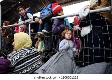 Idomeni, Greece - February 29, 2016. A refugee girl waits in line with other refugees to receive food, at the makeshift refugee camp of Idomeni, at the Greek - Macedonian border.