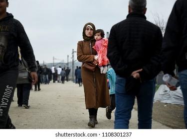 Idomeni, Greece - February 29, 2016. A refugee woman with her baby walks inside the makeshift camp of Idomeni, at the Greek - Macedonian border.