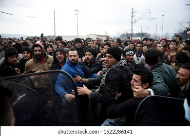 Idomeni, Greece - February 29, 2016. Refugees try to break a police blockade at the makeshift refugee camp of Idomeni in order to approach the Greek Macedonian border.